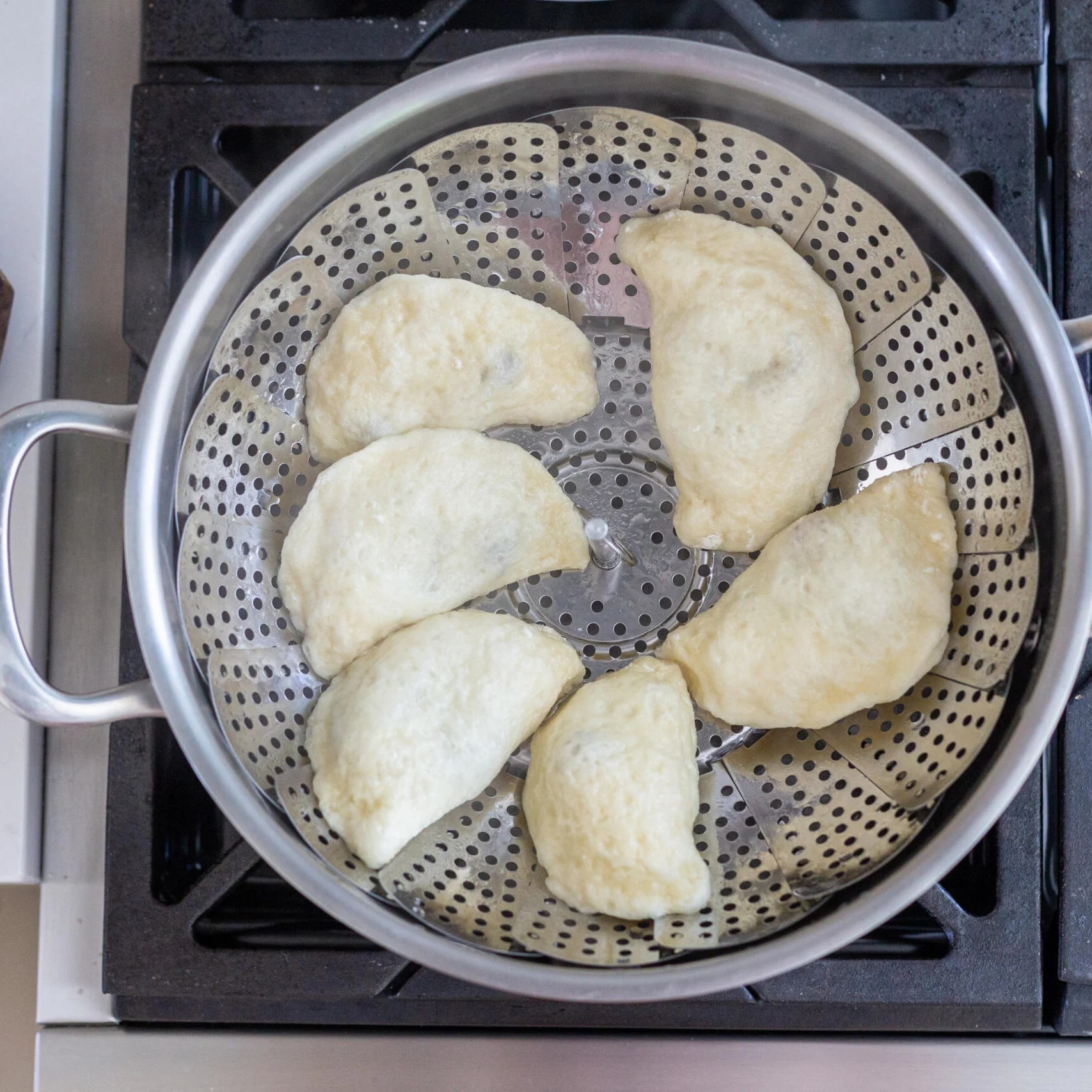 cooked pierogi in a pot with steamer