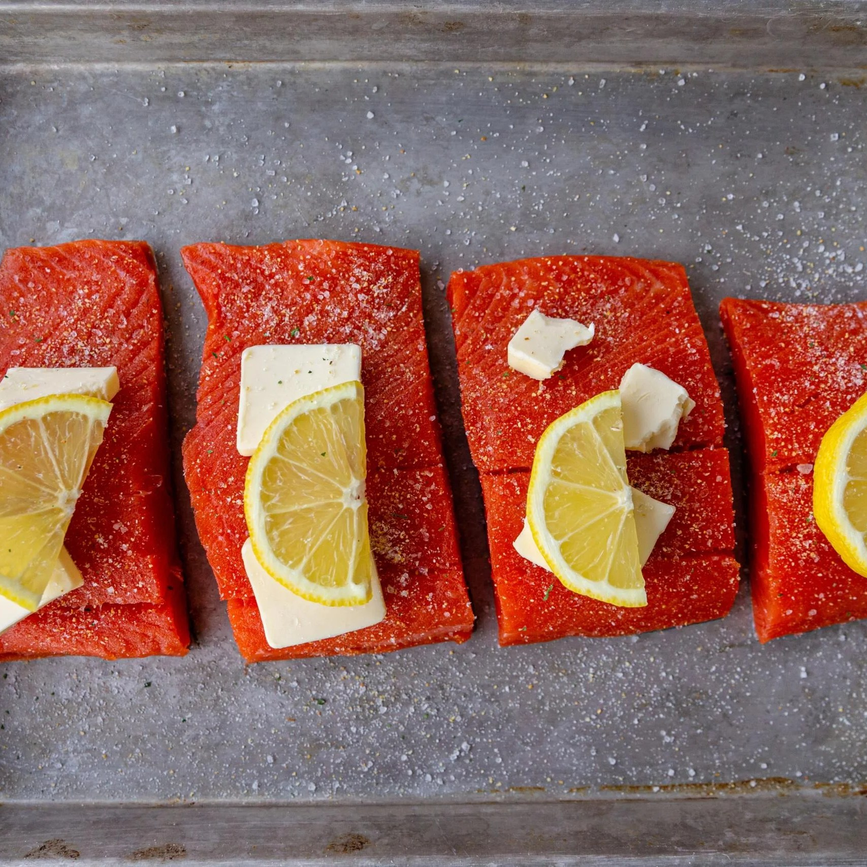 salmon pieces on a baking sheet with butter and lemon