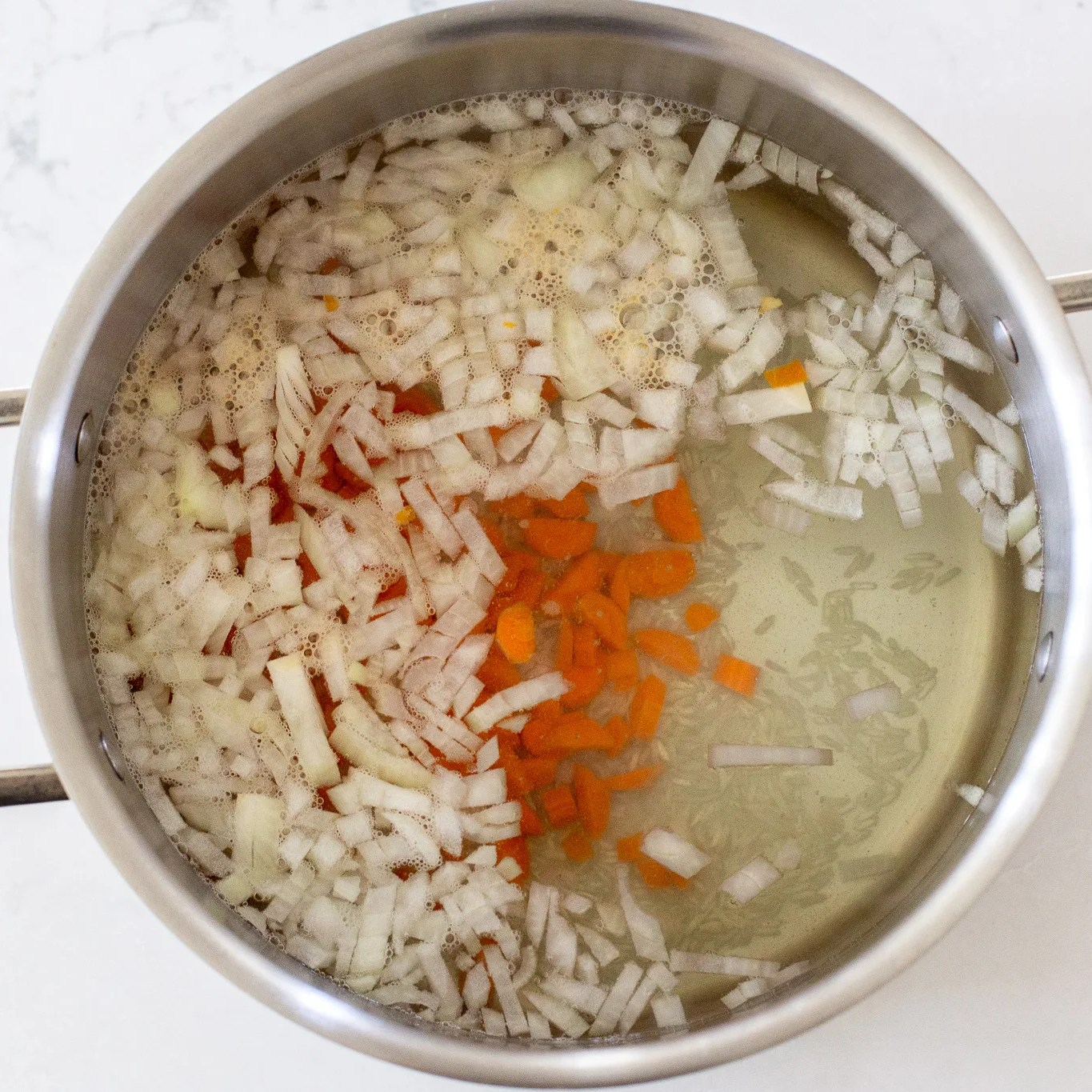 onions, carrots and rice in a pot with water