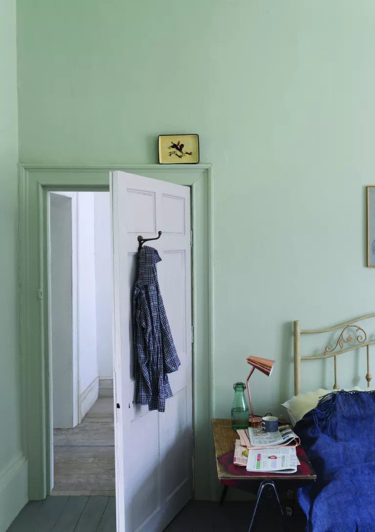 pale green grey bedroom with painted bed frame