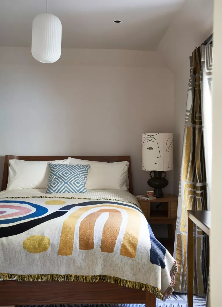 White bedroom with colorful abstract throw