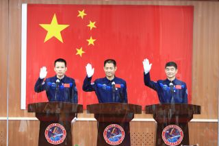 The crew of China's Shenzhou-12 astronaut flight to the country's new space station waves to reporters in a press conference at the Jiuquan Satellite Launch Center on June 16, 2021. They are (from left): Tang Hongbo, Nie Haisheng and Liu Boming.
