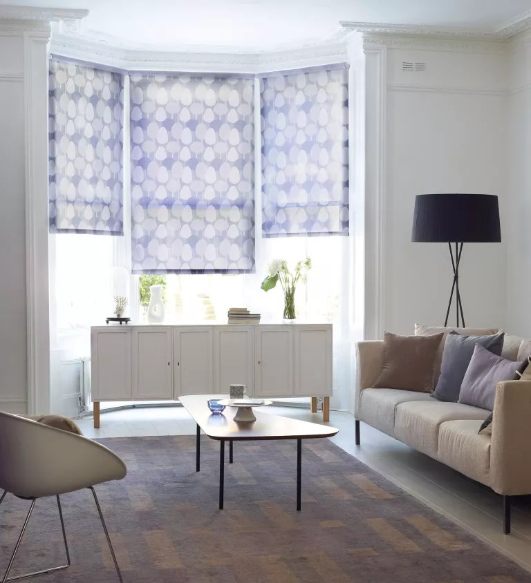 Blue patterned roller blinds on bay windows in white living room with accent floor lamp
