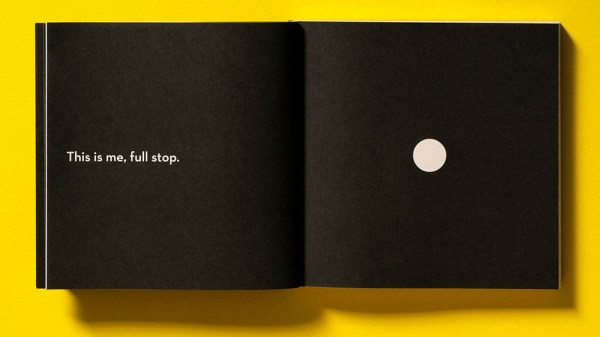 Open book with black background, small text on one page and big full stop on the opposite page