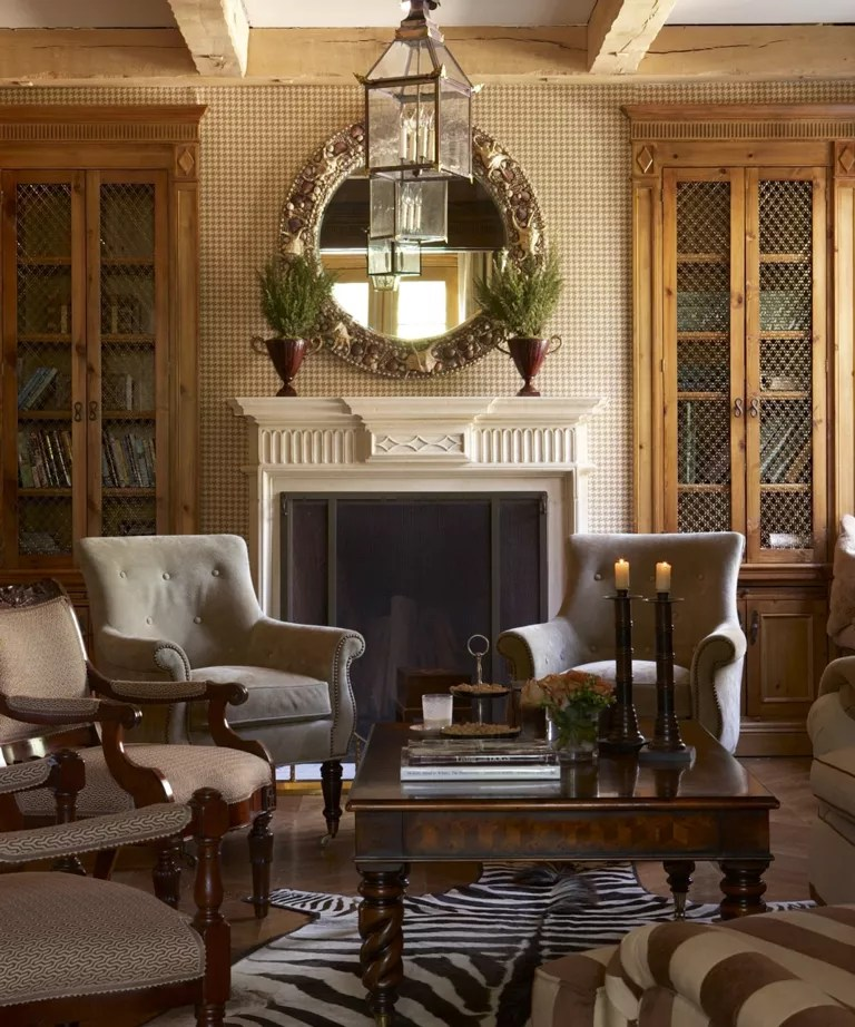 Fall mantel ideas with a brown traditional scheme, cream mantelpiece with foliage-filled wooden urns and circular mirror