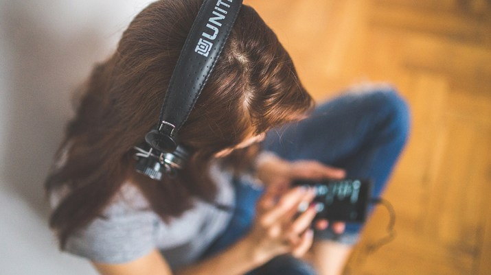 Photo of girl wearing headphones playing music on her phone