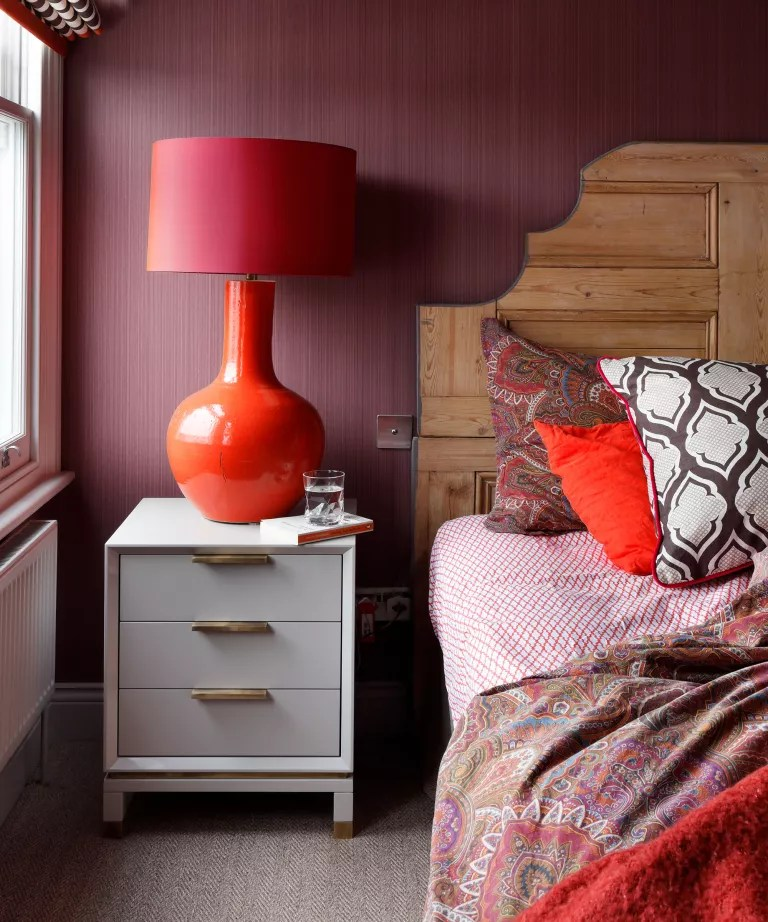 Red kids bedroom with textured wallpaper and red lamp