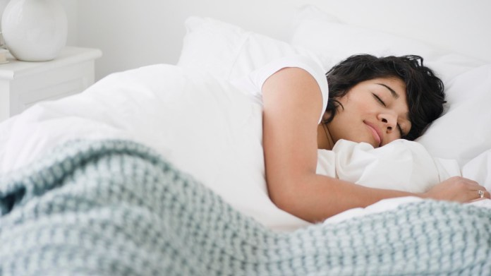 A woman with dark curly hair sleeps with a smile on her face