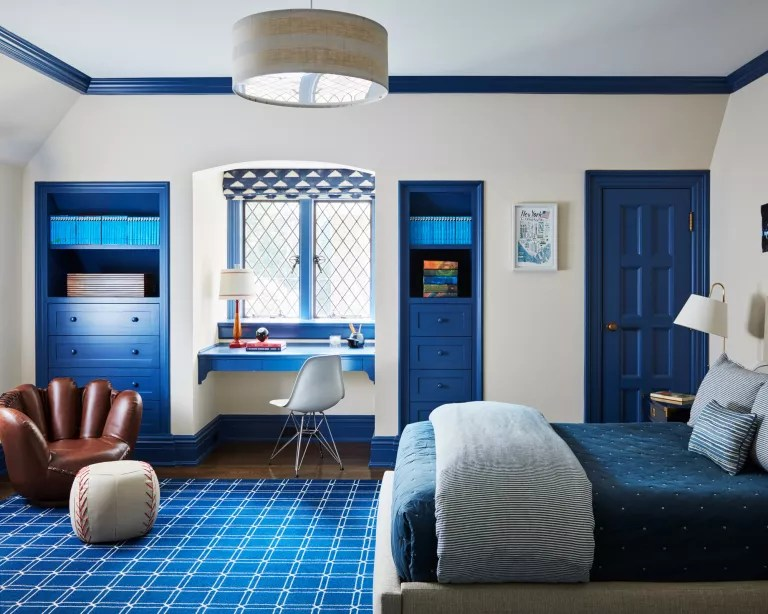 A child's bedroom with white wall, blue painted accents and a chair shaped like a baseball mit