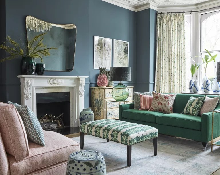 A living room mirror idea with green-blue walls and a bowed shaped mirror above fireplace