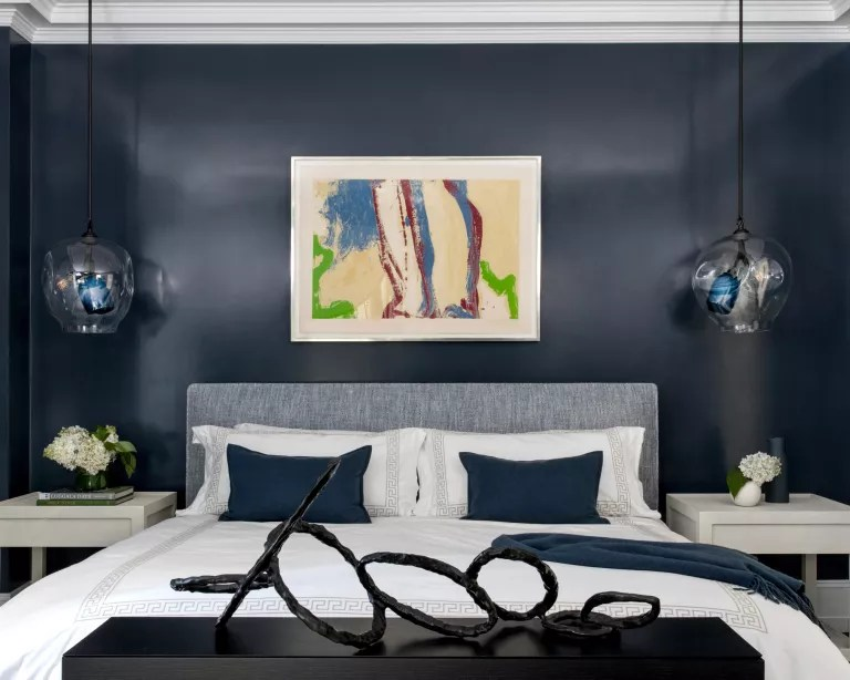 A master bedroom with navy gloss painted walls and statement artwork, including a sculpture at the end of the bed