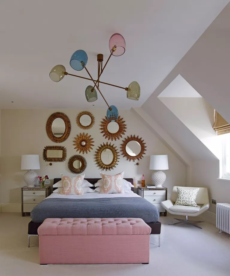 An example of bedroom ceiling light ideas showing a black bed in front of decorative gold wall mirrors and below a large blue, pink and green ceiling light