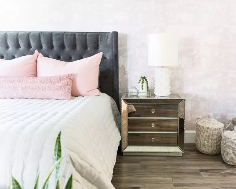 A bedroom with grey upholstered headboard and mirrored bedside chest of drawers