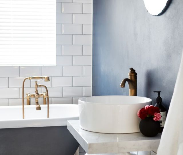 Bathroom With Navy Blue Wall And Marble Sink