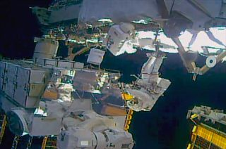 NASA astronauts Jessica Meir (foreground, in spacesuit with red stripes) and Christina Koch (with back turned to camera) work to upgrade batteries during a spacewalk outside of the International Space Station on Monday, Jan. 20, 2020.
