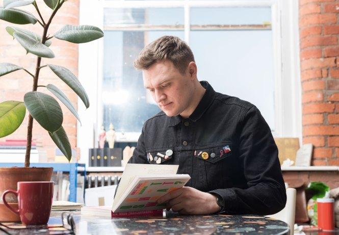 Craig Oldham reading at his desk