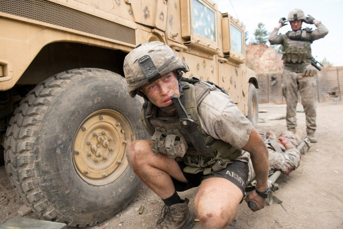 a solider kneeling while moving a body on a gurney in The Outpost, one of the best netflix war movies