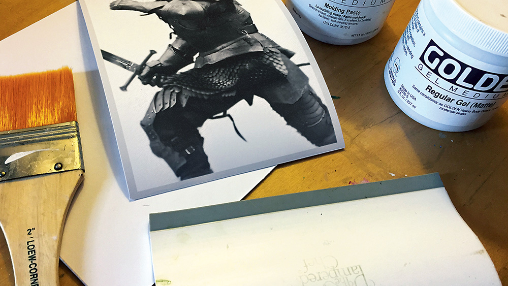 A print of the knight illustration, a wide paint brush and tubs of medium