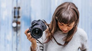Woman holding Canon EOS 6D Mark II