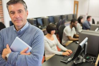 Male teacher in blue sweater stands in classroom with teens on computers in the background.