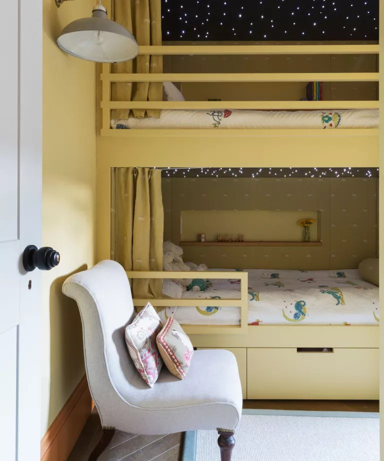 Kids shared bedroom ideas in yellow, with built-in bunk beds and a pale gray chair.