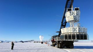 Researchers prepare to launch the Antarctic Impulsive Transient Antenna (ANITA) experiment, which picked up signals of impossible-seeming particles as it dangled from its balloon over Antarctica.
