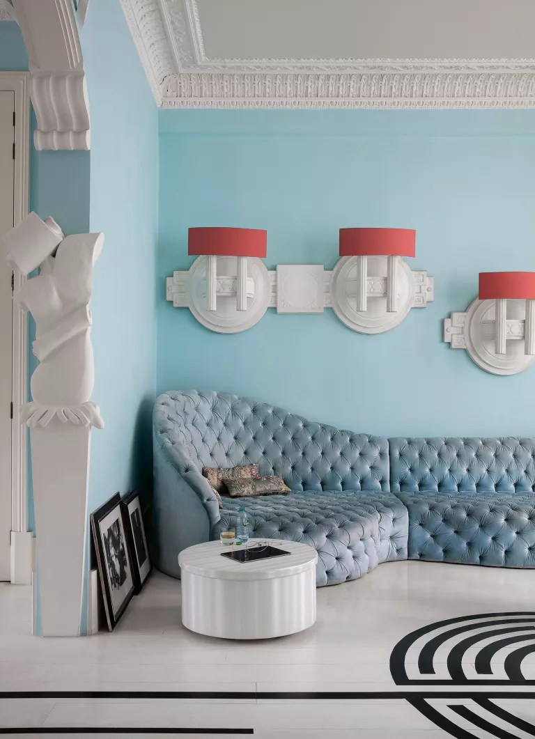 Pale blue living room with blue corner couch and orange wall lights