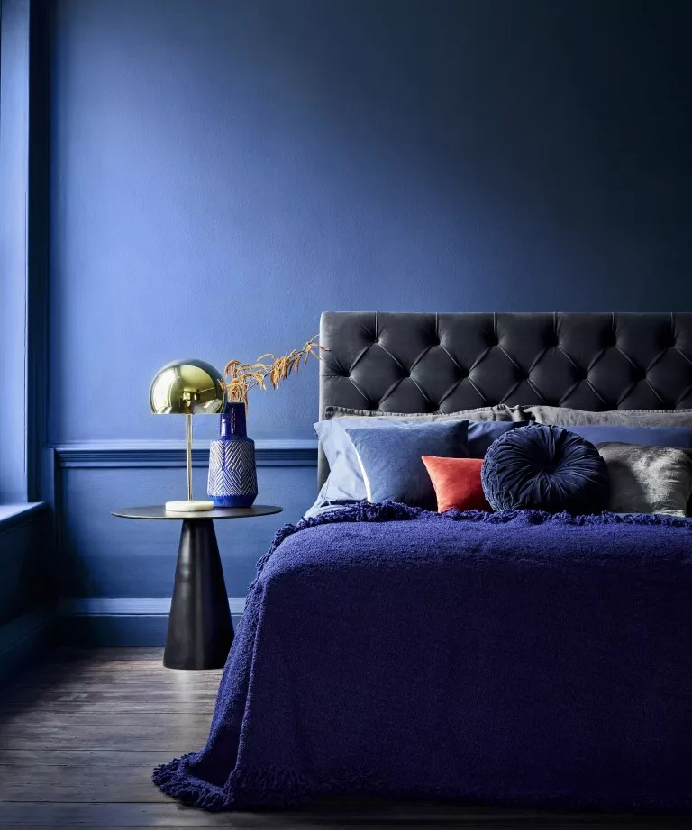 A dark blue bedroom featuring a bed with a blue velvet headboard