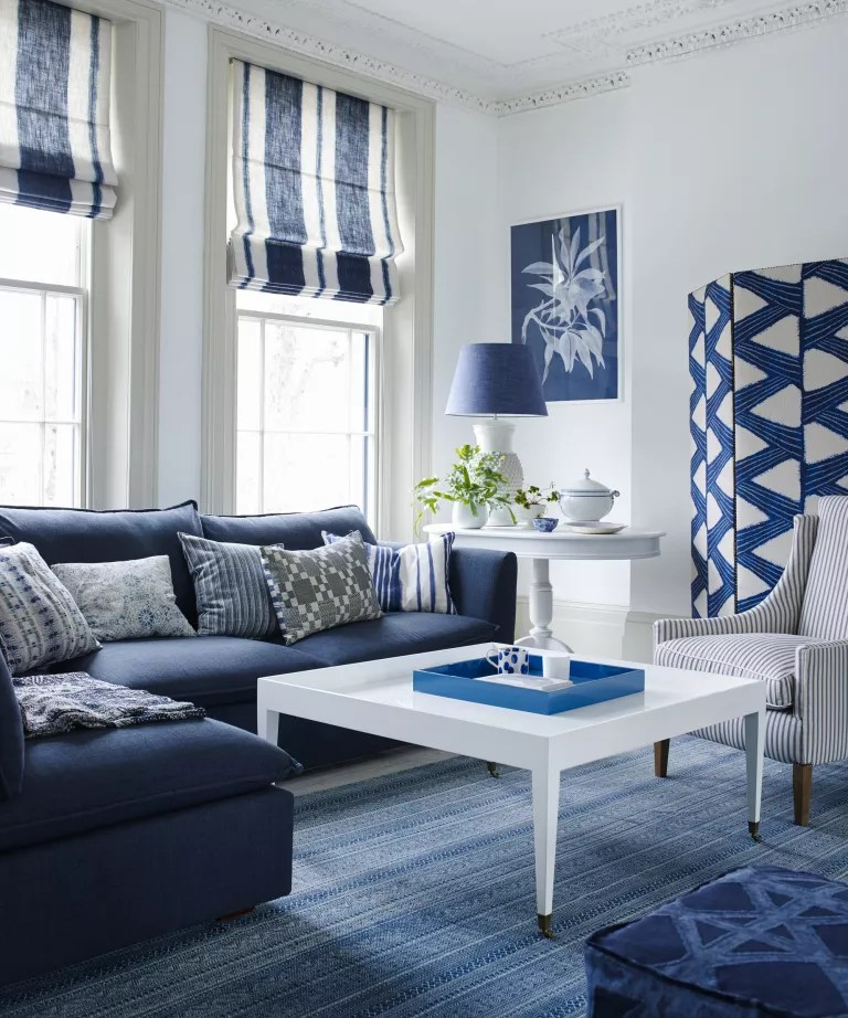 A monochromatic blue and white living room with blue sofas, printed screen and a woven rug