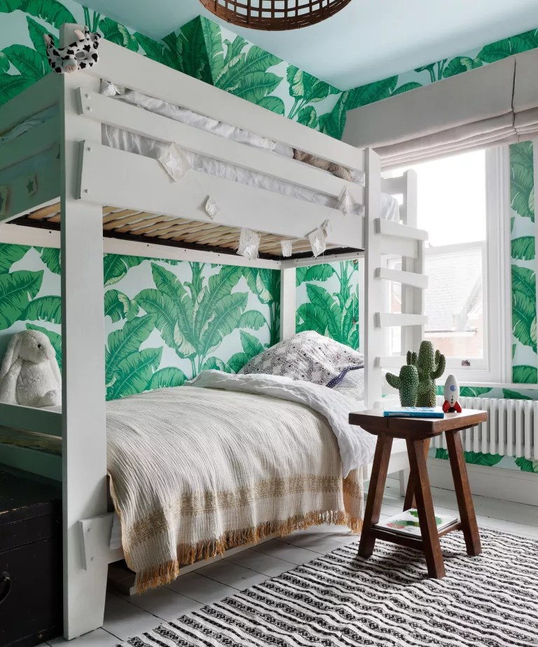 Kids shared bedroom ideas illustrated by a white bunk bed and large botanical-print green wallpaper.