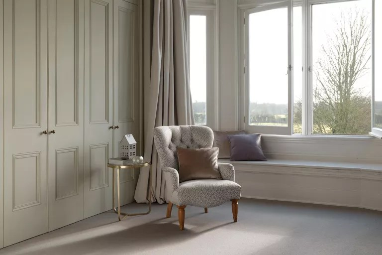 Neutral upholstered chair in carpeted bedroom space with light green built-in wardrobe doors, a seated bay window and gilded side table.