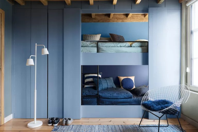 Shared bedroom idea with integrated bunks in painted blue wood in an all-blue scheme.