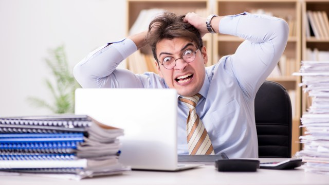Angry man ripping out his hair in front of his laptop