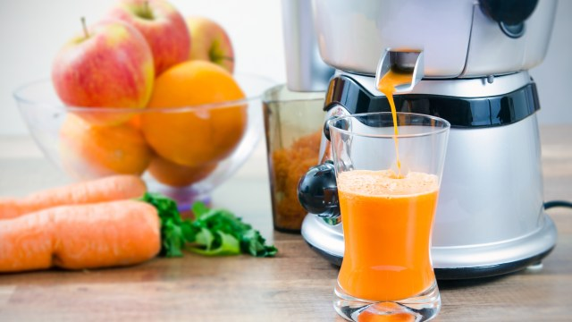 a Juicer being used to juice oranges and surrounded by fruit