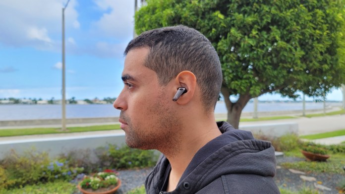The reviewer pictured wearing the Edifier NeoBuds Pro earbuds