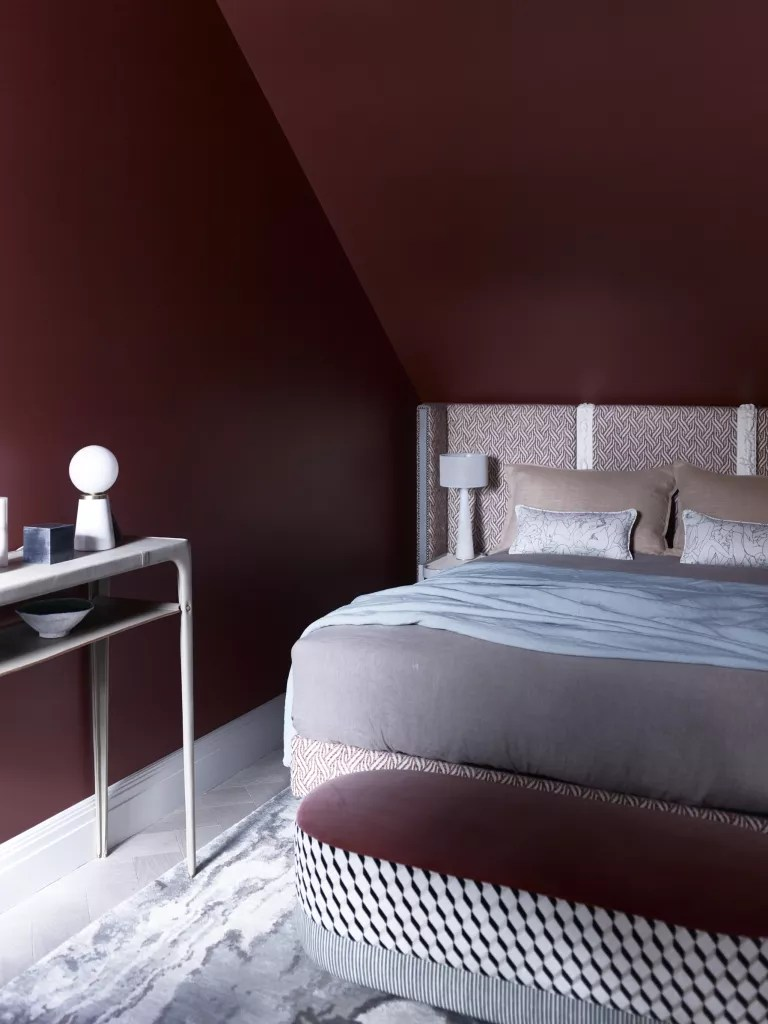 claret coloured bedroom with patterned bedhead and pale accessories