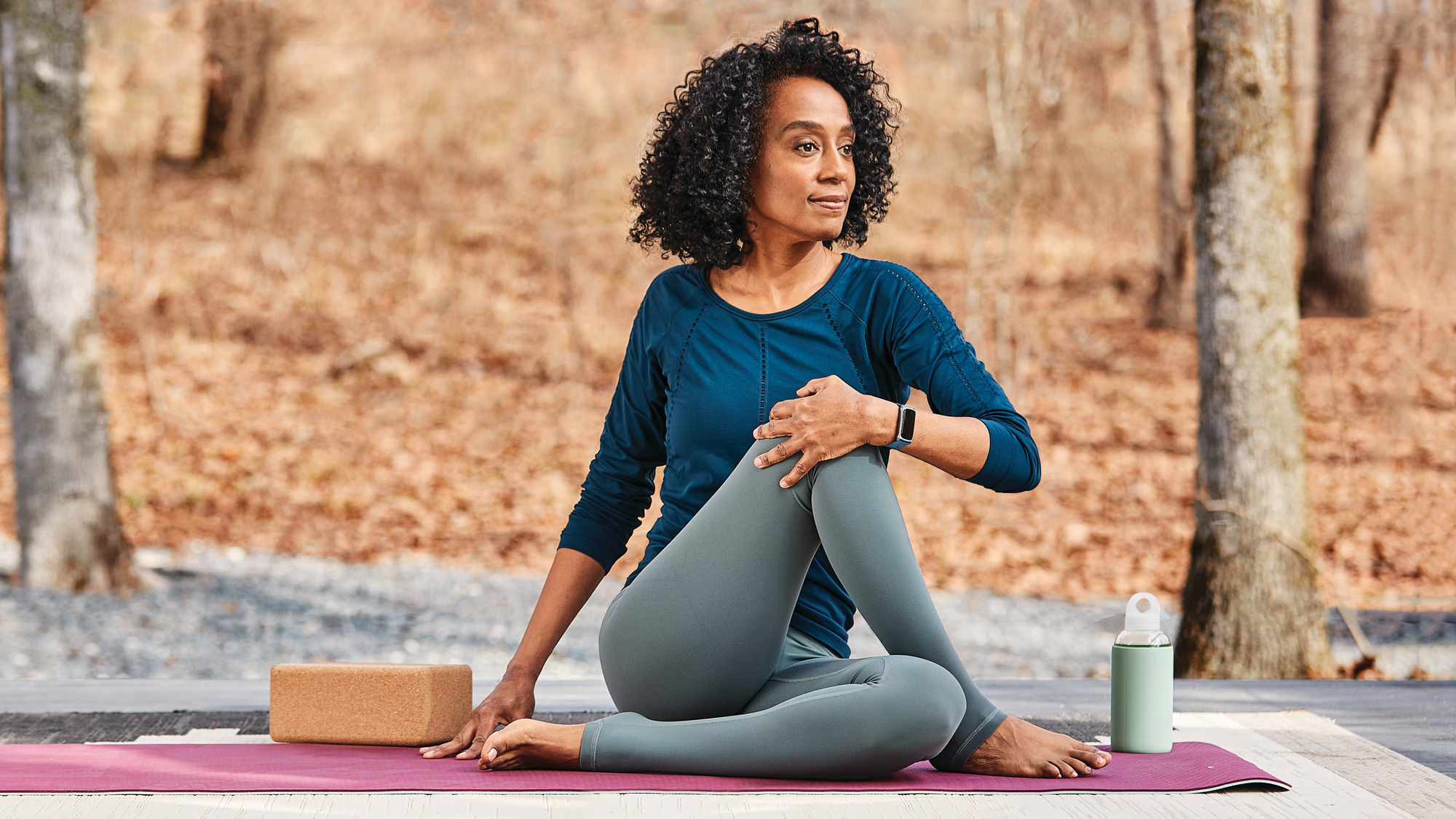 Woman doing yoga wearing Fitbit Charge 5