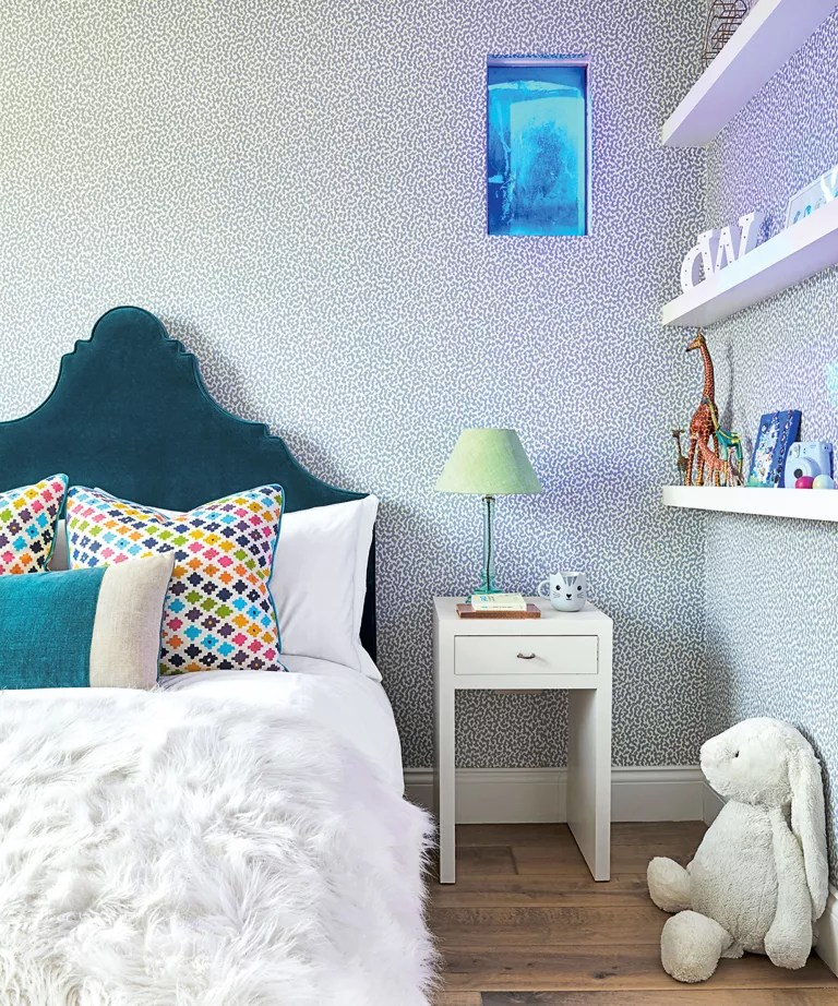 Kid's bedroom with blue headboard and shelving