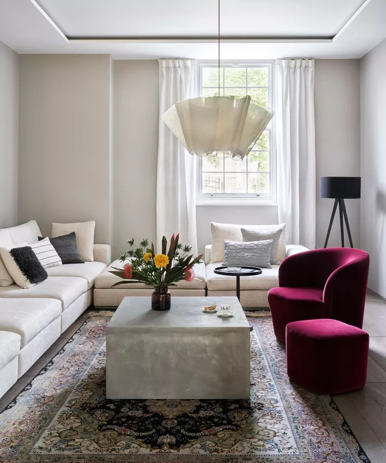 Minimalist living room with white walls and velvet armchair
