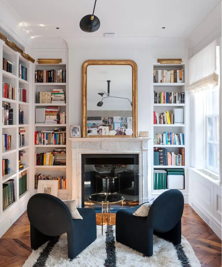 Built-in bookshelves and a pair of armchairs in a white scheme.