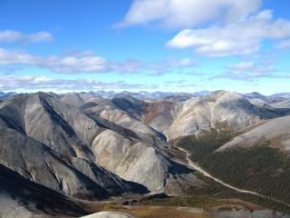 Plate tectonics is the means through which mountains are formed. Image shows rippled gray mountains, mostly treeless, beneath a cloud-studded blue sky. The Baird Mountains in Alaska's Kobuk Valley National Park formed when two tectonic plates along a convergent boundary collided, causing solid rock to buckle and fold.
