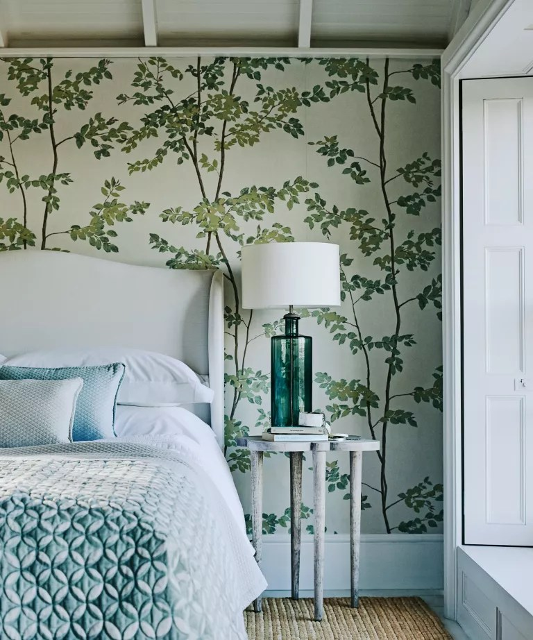 A bedroom with green-blue bed linen and a mural-like wallpaper covered in trees