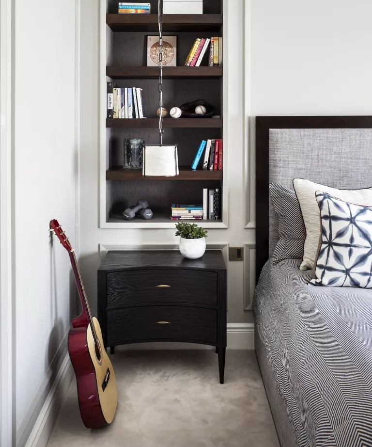 A bedroom with built-in open shelving next to the bed, over a black side table with drawers