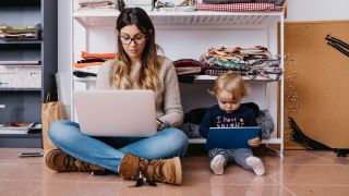 Mother and young daughter sitting on the floor at home using a laptop and tablet