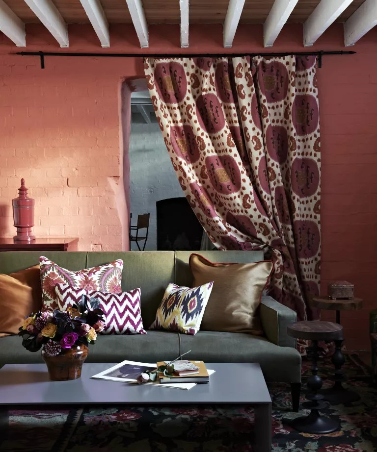 A living room curtain idea with red walls and internal curtain with pomegranate pattern
