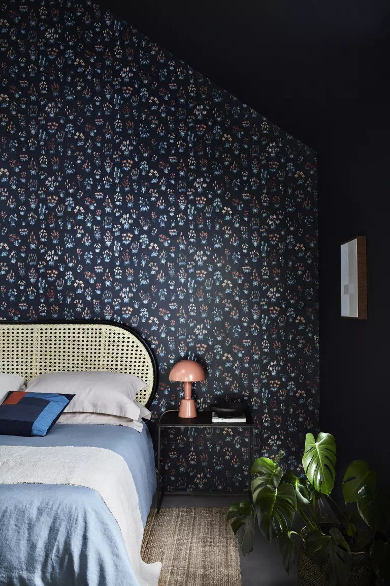 Dark blue wallpaper with small patches of flowers with pops of colors