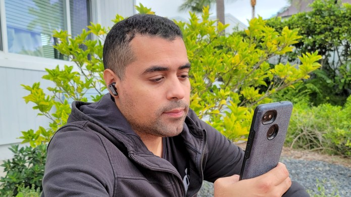 The reviewer wearing the Edifier NeoBuds Pro earbuds while looking at a smartphone