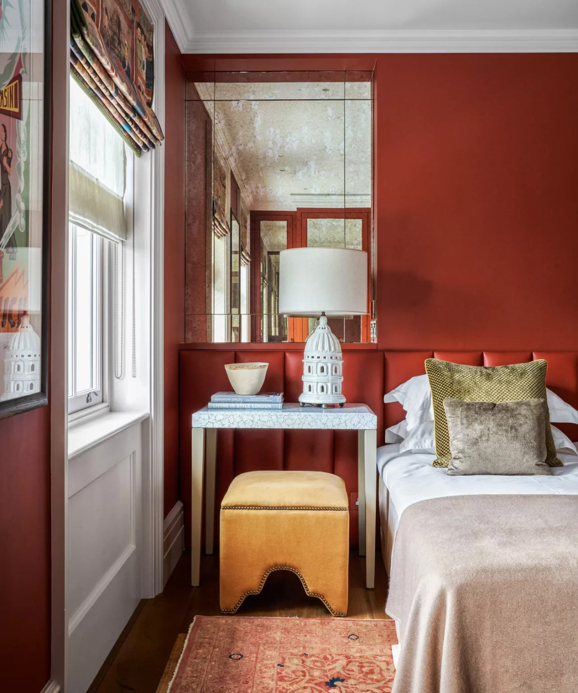 A fall color scheme in a bedroom with deep red walls, yellow stool and neutral bedding