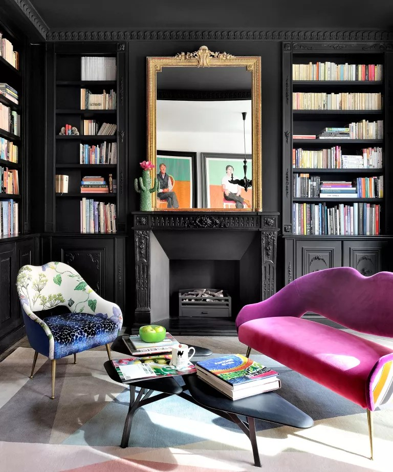 Black living room with pink sofa and bookcase