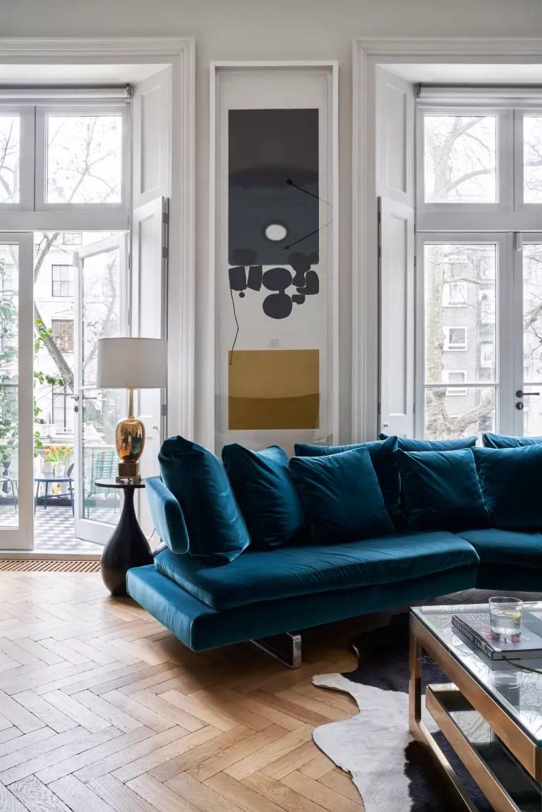 White living room with blue velvet sofa